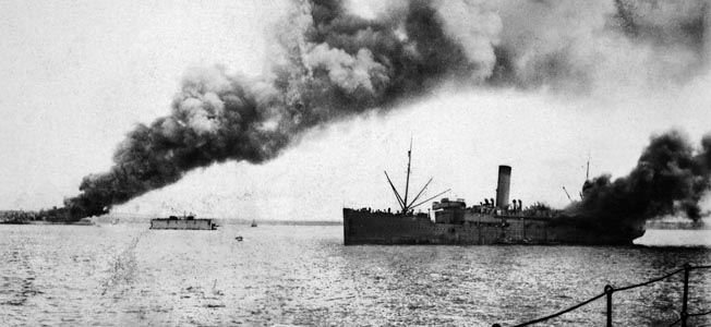 Smoke billows from Australian ships hit by Japanese bombers during the raid on Darwin harbor. In the foreground the troop transport SS Zealandia has been hit near the stern. In the distance, the cargo motor vessel Neptuna blazes.