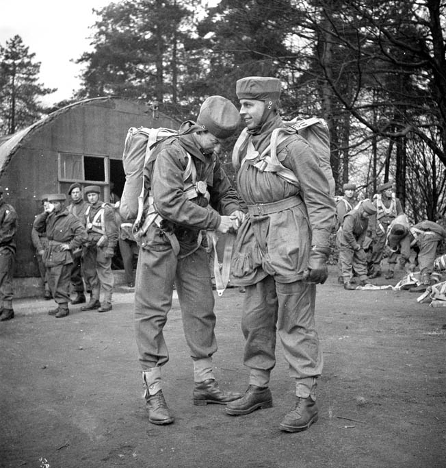 During a training exercise in April 1944, Major H. Fraser helps Lieutenant R.C. Hilborn of the 1st Canadian Parachute Battalion adjust his harness. This jump was conducted from a static balloon.