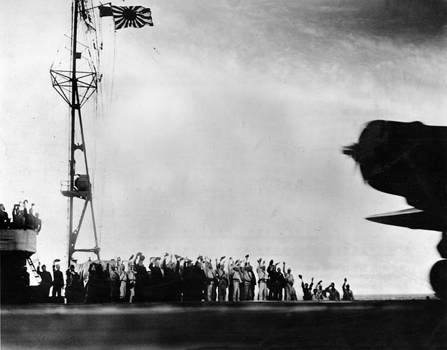 "Japanese crewmen aboard the aircraft carrier Shokaku cheer as a Nakajima B5N2 ""Kate"" torpedo bomber takes off for Pearl Harbor at about 7:00 am."