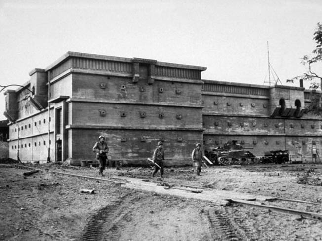 American soldiers advance cautiously past a large concrete air raid shelter in the city of Aachen. The shelter was occupied by German civilians and soldiers seeking to escape the heavy bombing and continual artillery bombardment that preceded the capitulation of the city.