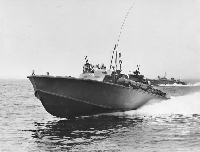 PT-105 is seen among a group of PT boats on maneuvers in the Atlantic shortly after completion in July 1942. The initial group of boats had no armament forward of the conn area, but the space was used later in the war for more firepower.