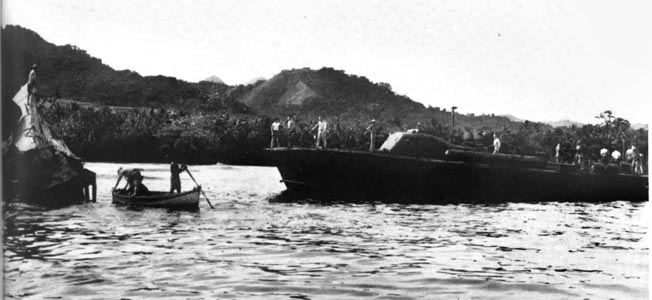 Crewmen aboard the PT-59, one of the swift U.S. Navy craft that took part in the December 7, 1942, action against Japanese destroyers, inspect the wreckage of a Japanese submarine in February 1943. During that month the Japanese abandoned Guadalcanal and acknowledged a significant defeat during World War II in the Pacific.