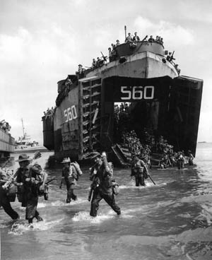 Australian troops pour ashore on Borneo from an American LST (Landing Ship, Tank), July 1, 1945. The PT boats of Squadron 27 provided close-in support to the invasion force.