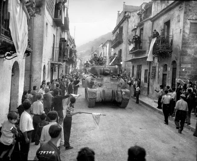 Cheering crowds greet American tankers as they roar through the streets of Palermo, Sicily. Bromberg compared entering the city to a big parade with free wine.