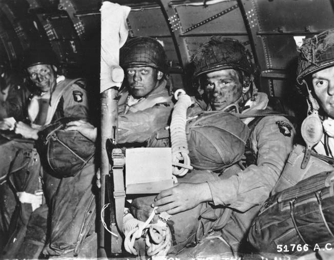 Heavily armed paratroopers of the 101st Airborne Division await the signal to stand up and hook up. Their faces are blacked to camouflage them during the night assault.