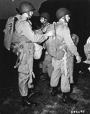 Paratroopers check their gear prior to loading aboard Douglas C-47 transport aircraft for the jump into Normandy during the predawn hours of D-Day. The transport aircraft came under heavy fire and encountered high winds, causing them to fly low and fast and scattering their human cargo across a wide area of Normandy.