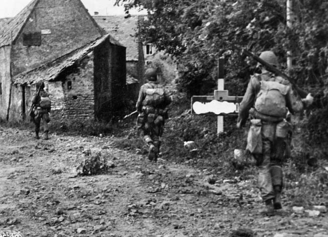 During the predawn hours of June 6, 1944, American paratroopers advance warily down a dirt road and into a small village.