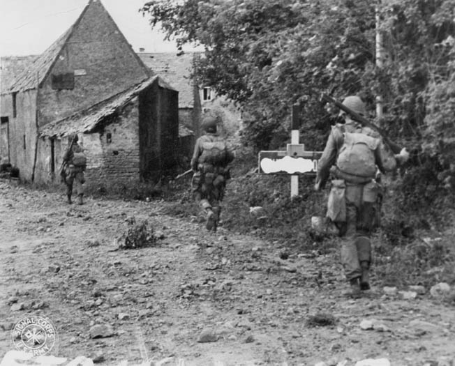 American paratroopers move cautiously into a Normandy village, June 1944. An Army censor has blocked out the name of the village on the signpost.