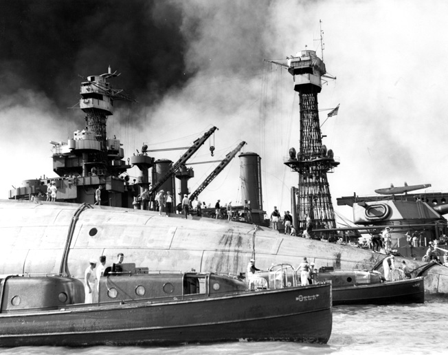 Frantically working to cut through the hull and reach sailors trapped inside the capsized battleship USS Oklahoma, men employ blowtorches and listen for the tapping of distress signals. The effort to reach the trapped sailors went on for several days.