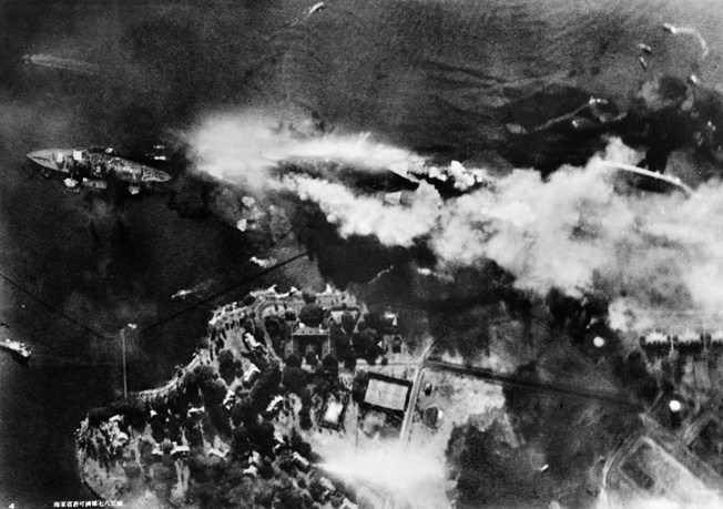 This harrowing photograph of Battleship Row under attack on the morning of December 7, 1941, was taken from a Japanese plane. Adjacent to Ford Island in Pearl Harbor lies the battleship USS Nevada at left, while the USS Arizona belches smoke and flame to the right. Outboard of the Arizona is the repair ship USS Vestal. Continuing left to right, the USS West Virginia is outboard of the USS Tennessee while the capsized USS Oklahoma sits outboard of the USS Maryland.