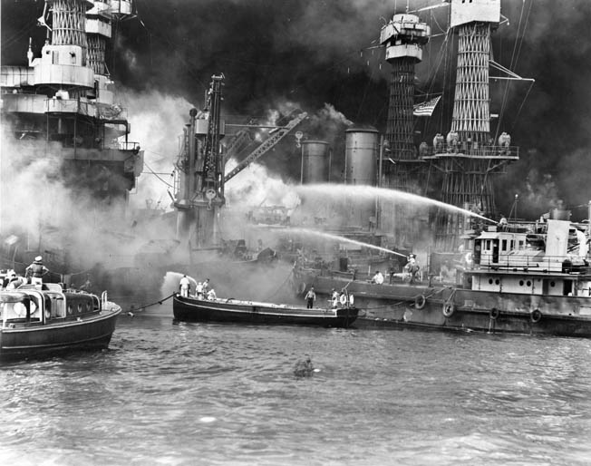 Fireboats pour water on the West Virginia (BB-48) while motor launches rescue sailors in the water.