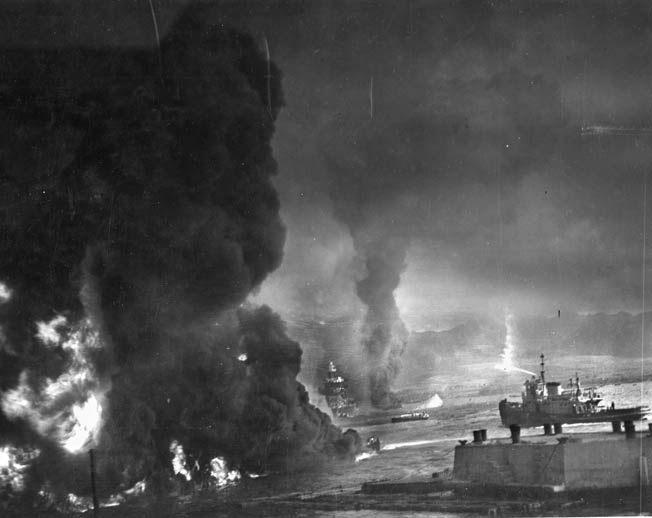 A fireboat (right) attacks the flames and black smoke shrouding the battleship Maryland. In the distance another damaged battleship (probably West Virginia) and the capsized Oklahoma are visible.