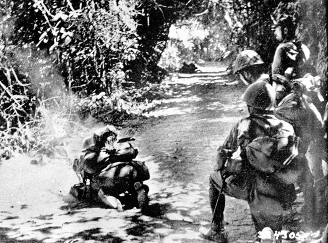 Soldiers of the Japanese 14th Army peer warily down a dirt road during their advance along the Bataan Peninsula.