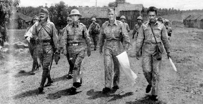 Two unidentified American officers are escorted to a surrender ceremony on the Bataan Peninsula.