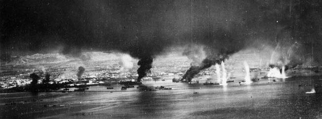 Fires send black smoke aloft from Japanese ships and facilities at Manila Bay on November 13, 1944, following an attack by SB2C Helldiver dive-bombers.