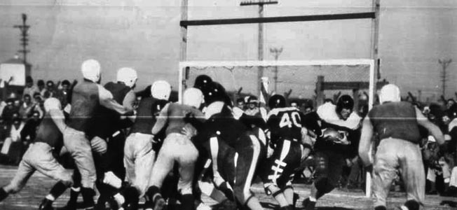 "A newspaper photo of action during the ""Barbwire Bowl Classic"" played at Stockton Ordnance Depot POW camp on January 13, 1946."