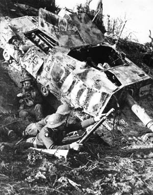 As one of their comrades attempts to establish communications via walkie-talkie, a pair of Polish soldiers mans a two-inch mortar on an Italian hillside. The Poles have taken cover adjacent to a destroyed German self-propelled gun.