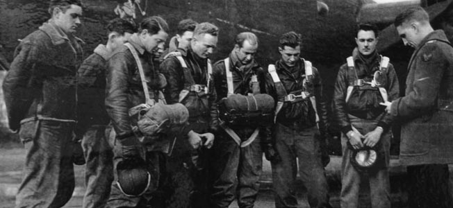 Eighth Air Force chaplain James Burris (right) leads the crew of the Lonesome Polecat in prayer before they take off on a mission.