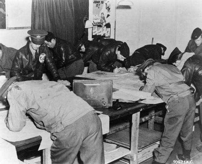 Officers of the 93rd Bombardment Group, based at RAF Hardwick, study target maps prior to a mission. The group lost 100 aircraft and nearly 1,000 men during the war.