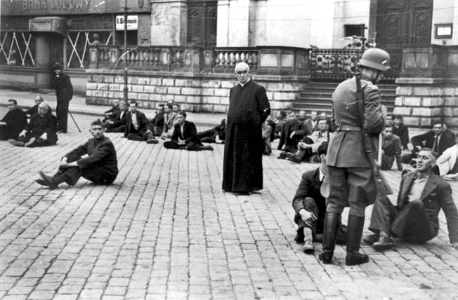 A priest waits with Polish civilians rounded up by Nazis in Bydgoszcz, Poland, in September 1939. These men were likely executed.