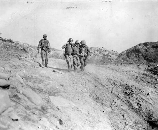 Two G.I.s assist a fellow wounded soldier. The battle for Pork Chop Hill in many respects was a fight dominated by artillery, mortar fire, and tactical air strikes.