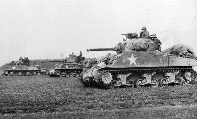 American Sherman tanks halt momentarily near the village of Prummeran, east of Geilenkirchen. Nearly 50,000 Shermans were produced during World War II, and the tank became an Allied workhorse.
