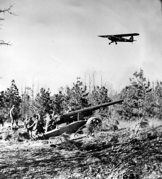 "An L-4 Piper Cub spotter plane, nicknamed the ""Grasshopper,"" flies over a 155mm artillery battery of the 36th Field Artillery Regiment during training at Fort Bragg, North Carolina. The small, slow-moving aircraft could bring accurate fire down on enemy positions——often with great danger to the pilots and observers."