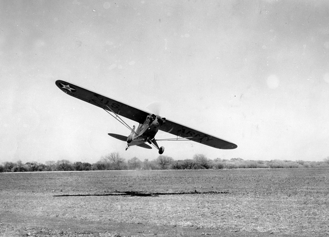 Not requiring a hard runway, an L-4 lands in a field.