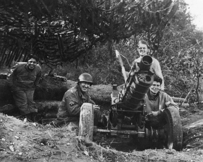 Gunners from C Battery, 376th Parachute Field Artillery Battalion pose with their 75mm pack howitzer some- where in Holland, 1944.