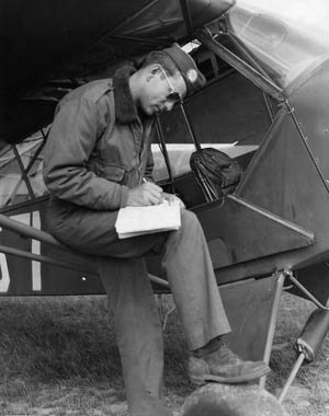 Lieutenant Albert M. Boulanger, a pilot for 376th Parachute Field Artillery Battalion, 82nd Airborne Division, fills in his logbook after a mission.