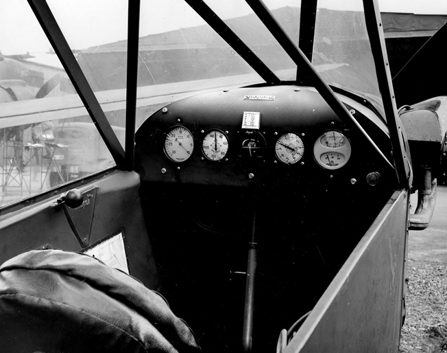 Uncluttered cockpit: tachometer, airspeed indicator, liquid compass, altimeter, and oil temperature/ pressure gauge.