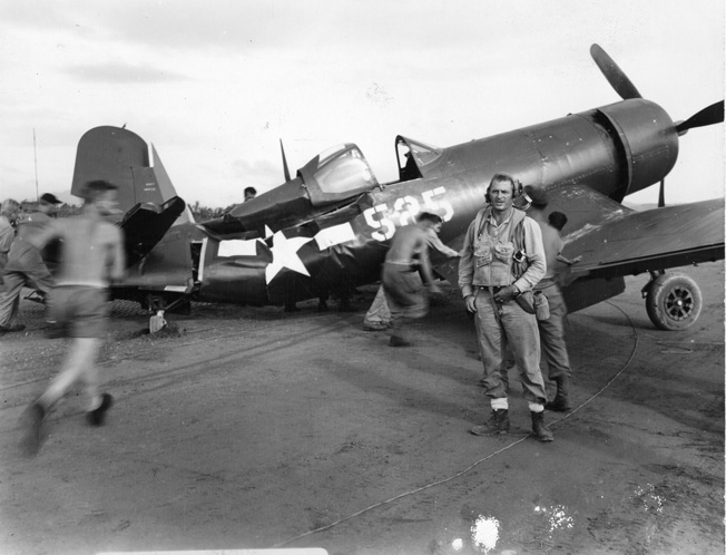 Here, Marine Major Theodore Olsen, commanding officer of VMF-313 (right), stands in front of his badly damaged Corsair. He was later killed in action.