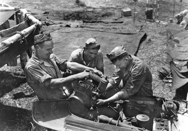 Marine mechanics at an air field work on a jeep engine.