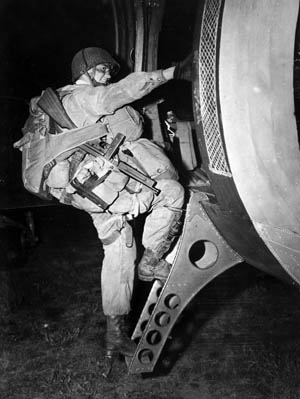"""T/4 Joseph Gorenc, a heavily laden paratrooper with HQ Company, 3rd Battalion, 506 Parachute Infantry Regiment, 101st Airborne Division, flashes a confident smile as he hoists himself into one of hundreds of C-47 """"Skytrain"""" transport air- craft that were used to carry troops and gliders to Normandy on the night of June 5-6 1944."""