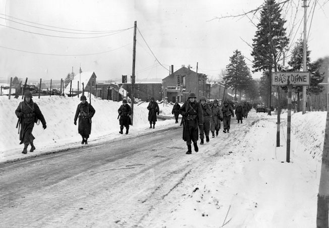 """Members of a """"Screaming Eagles"""" unit move out of snowy Bastogne on December 29, 1944, to attack enemy holed up in a nearby village. Note the bullet- scarred city limit sign."""