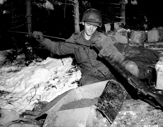 Surrounded by snow, Private First Class William Ottersbach of the 101st cleans his rifle near Foy, Belgium, January 11, 1945.