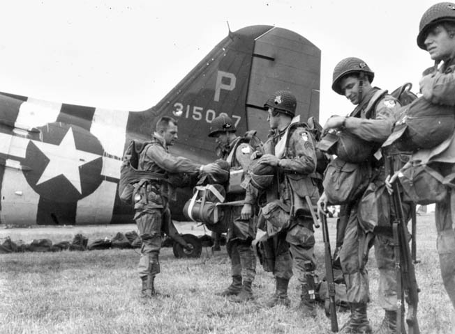 A jumpmaster checks the reserve 'chutes and equipment of paratroopers about to board a C-47. Note that a military censor has obscured the unit patches on the men's left sleeves.