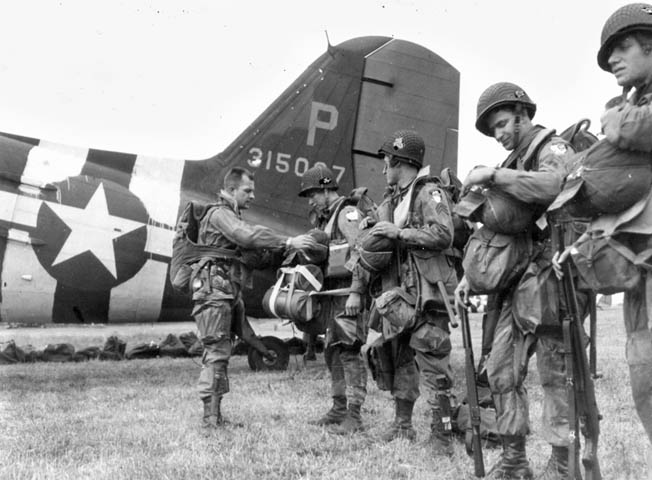 A jumpmaster checks parachutes and equipment of paratroopers preparing for the Normandy airdrop. The 101st Division was tasked with gaining control of the causeways leading out of Utah.