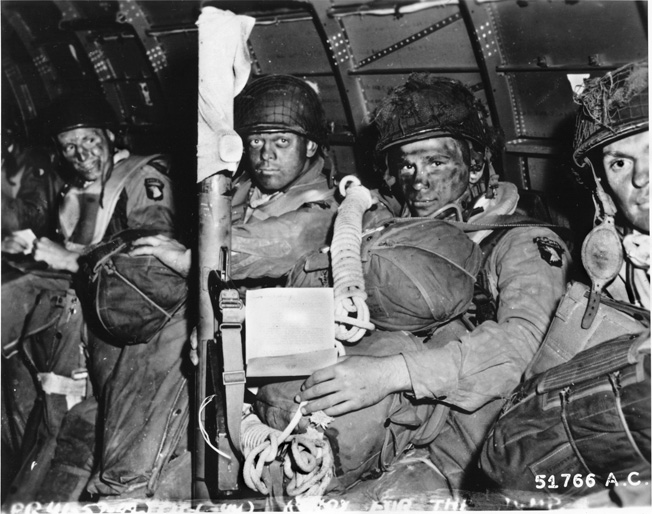 """With blackened faces, a """"stick"""" of 101st Airborne troops prepare to depart England. The bazookaman in front holds a copy of Eisenhower's inspirational message for Operation Overlord."""