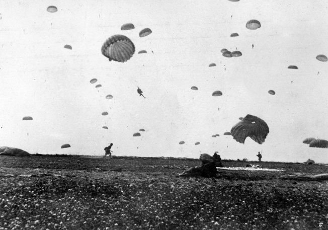 The sky of Holland is filled with American paratroopers while others are already out of their harnesses and running off the drop zone toward their assembly areas.