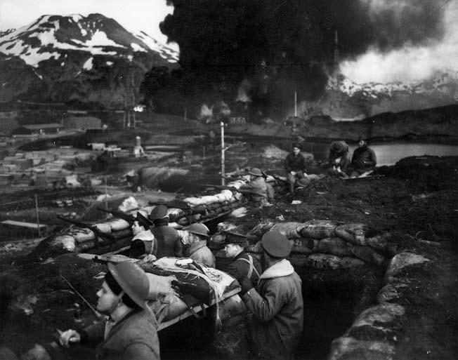 U.S. Marines man their sand-bagged trenches in anticipation of another enemy attack on Dutch Harbor while smoke rises in the background from burning fuel tanks, set afire by a dive bomber.