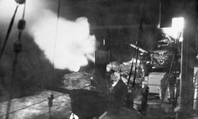In the dark: The Australian cruiser Canberra conducting a night-firing drill. Canberra fired only a few rounds before she was left dead in the water.