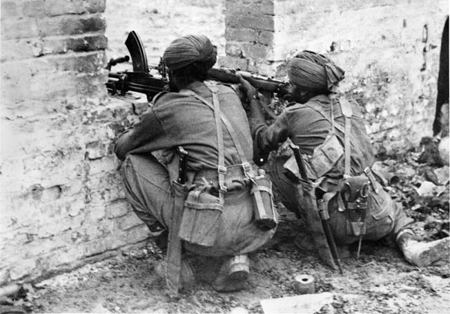 Sikh troops of the 19th Indian Division battle for Fort Dufferin. A formidable stronghold a mile square with 30-foot-tall ramparts and a 70-yard-wide moat, the fort fell after 12 days of heavy fighting.