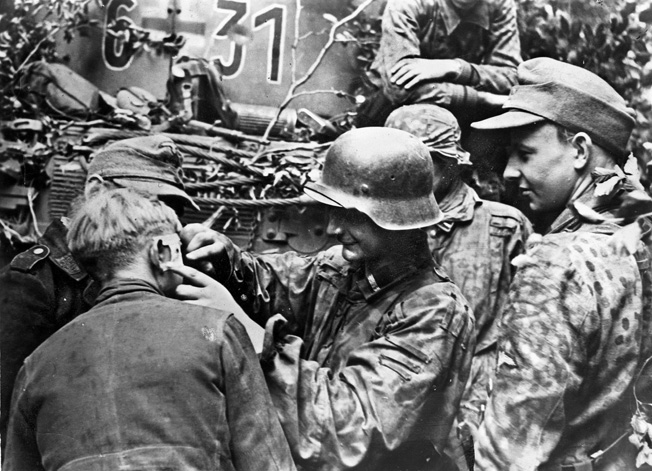 "With his comrades looking on, a wounded soldier of the 12th SS Panzer Division (""Hitlerjugend"") receives medical attention during a lull in the battle for Juno Beach."