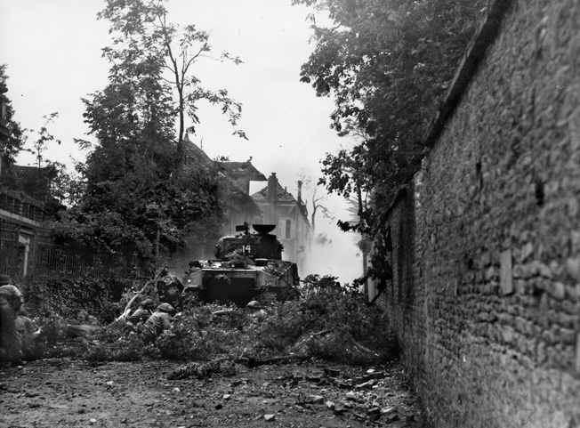 "Soon after landing at Juno Beach, Canadian troops became hotly engaged in urban fighting in a multitude of small towns and villages. Here Canadian soldiers, using a ""Grizzly"" medium tank (the Canadian variation of the M4 Sherman) for cover and fallen tree branches for concealment, advance toward an enemy-held French town."