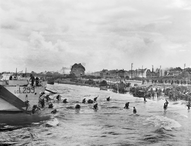 More 9th Brigade troops, some carrying bicycles, wade ashore at Juno Beach. Many of the bikes were soon abandoned by the soldiers who found they attracted German fire.