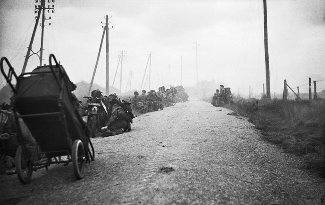 Canadian infantrymen, some with motorcycles and bicycles, along with men from the Royal Marine Commandos, crouch on a road during a German mortar attack early on D-Day.