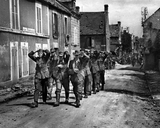 German soldiers, captured by Canadian troops in Normandy, are marched back to a prisoner-of-war holding pen. The Germans did not always treat captives according to the rules of war, as several massacres of Allied troops would soon prove.