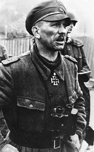 "Commanding SS-Panzergrenadier Regiment 25 was Standartenführer (Colonel) Kurt ""Panzer"" Meyer, shown in 1943. A rabid Nazi, he was tried for war crimes in 1945 and condemned to death, but was later released."