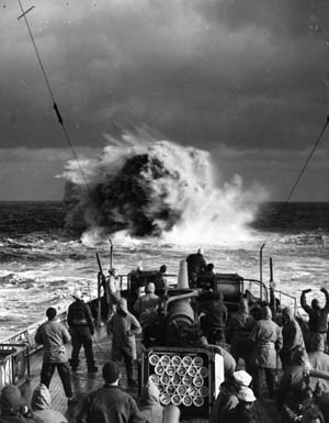 American sailors watch as the explosion of a depth charge roils the water during a drill in the North Atlantic.
